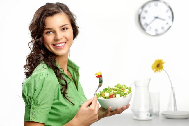 Девушка держит в руках миску с салатом