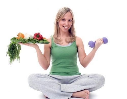 Девушка держит в руках гантелю и тарелку с овощами