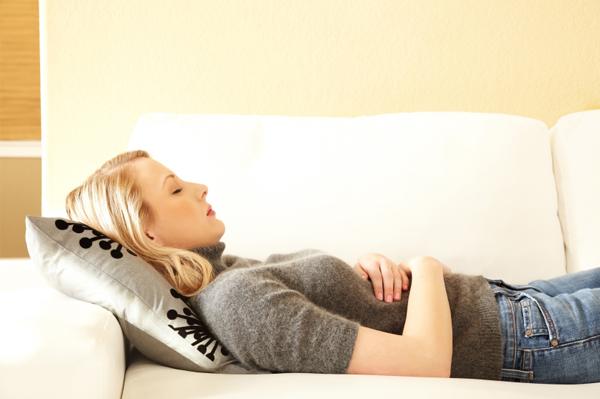 Женщина лежин на диване, сложив руки на животе