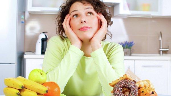 Девушка сидит за столов с фруктами и выпечкой