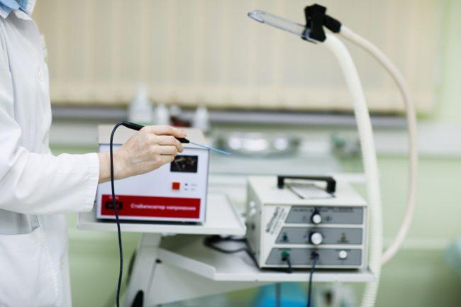 Врач держит в руках радиоволновой аппарат
