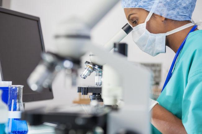 Женщина в лаборатории за микроскопом