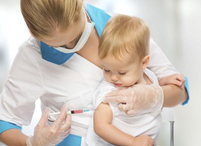 Медсестра делает укол ребёнку в область плеча