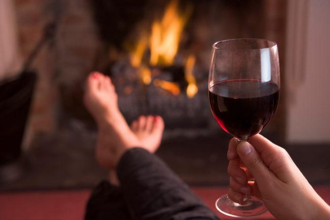 Бокал вина в руке на фоне камина